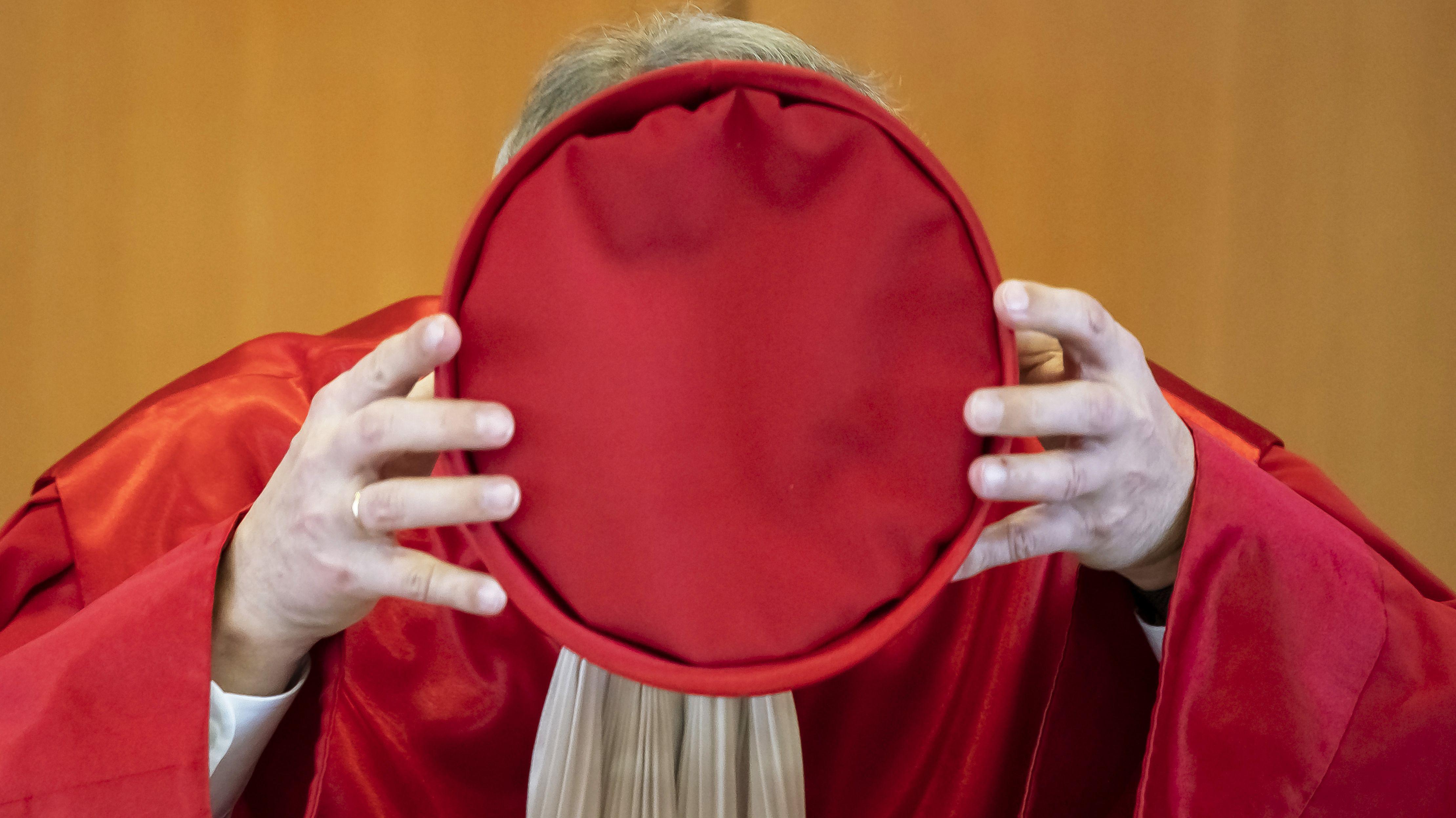 Ein Mann in einer roten Robe hält eine rote Mütze vor seinem Gesicht.