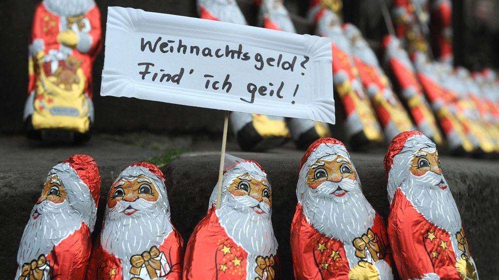 """Schoko-Nikoläuse mit einem Schild """"Weihnachtsgeld? Find' ich geil!""""   Bild:dpa-Bildfunk/Ingo Wagner"""