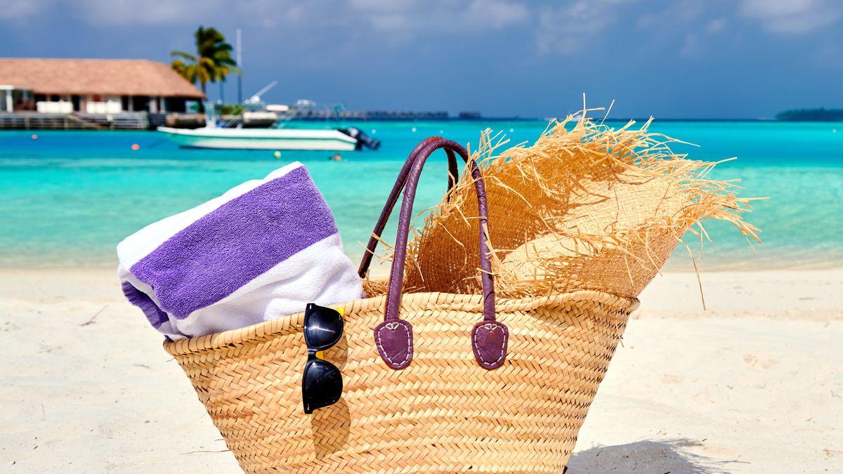 Strandkorb mit Sonnenbrille, Sonnenhut und Handtuch. Dahinter das Meer und ein Boot.