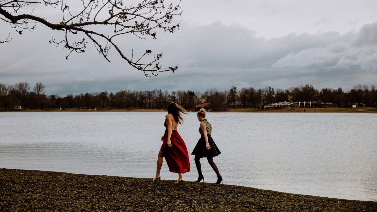 Zwei Frauen gehen in Abendkleidern spazieren.