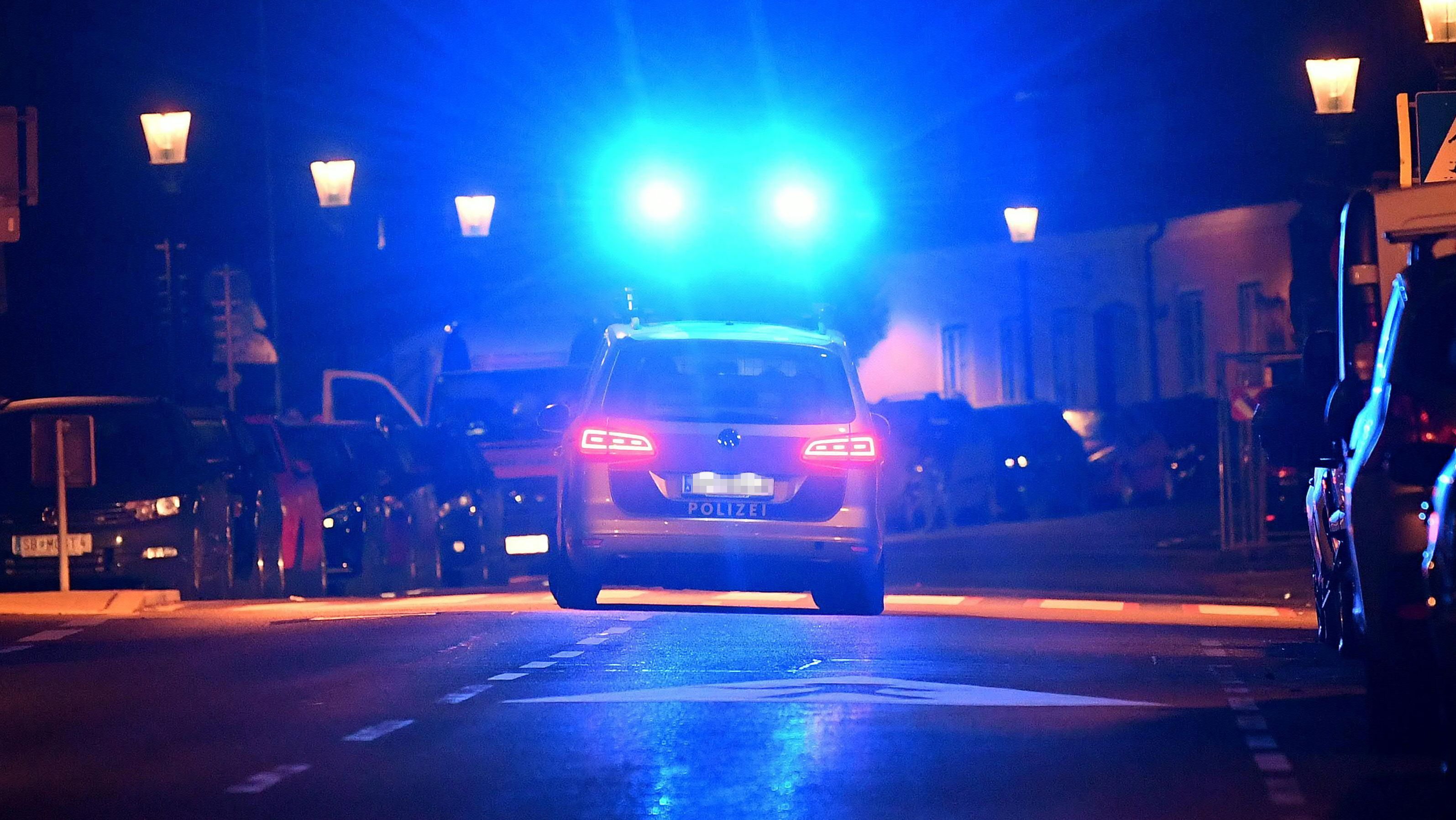 Ein Polizeiauto fährt nachts mit Blaulicht eine Straße entlang.