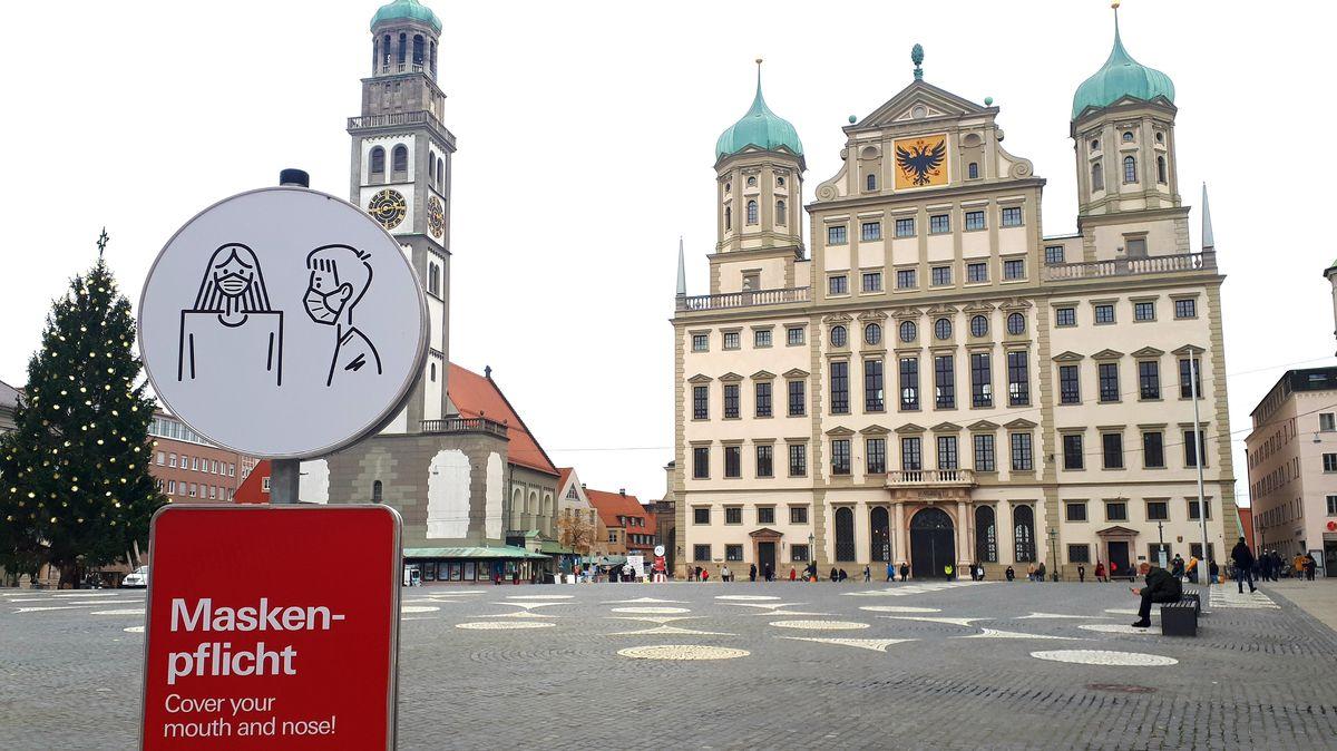 Das historische Rathaus in Augsburg und der Perlachturm. Im Vordergrund weist ein Schild auf die Maskenpflicht hin. (Archivbild, November 2020)