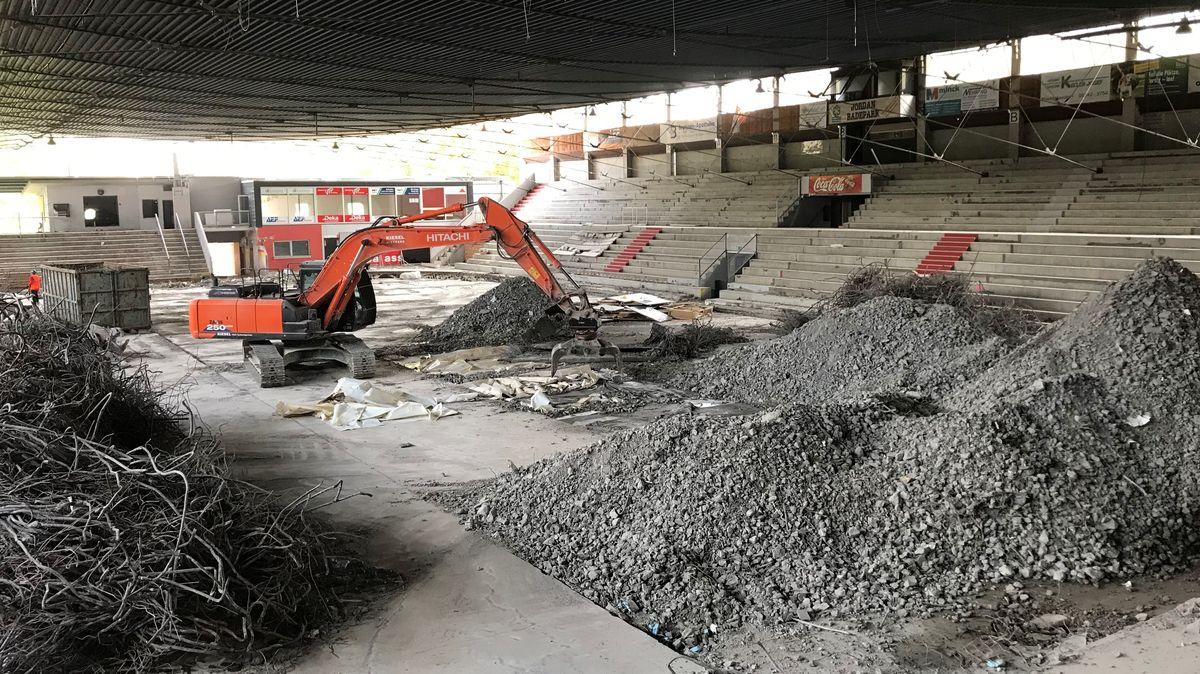Ein Bagger sammelt im Inneren des alten Eisstadions in Kaufbeuren Schutt auf.