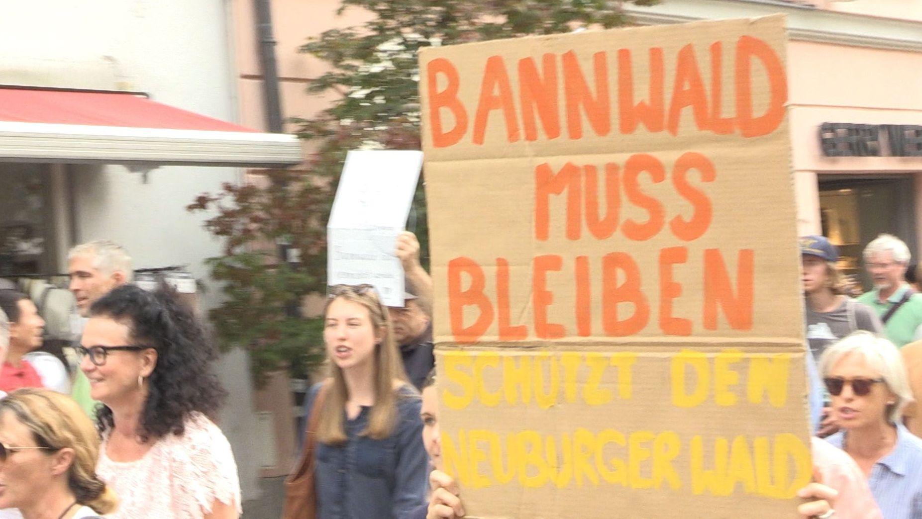 """Im Demonstrantionszug wird ein Plakat mit der Aufschrift """"Bannwald muss bleiben"""" hochgehalten"""