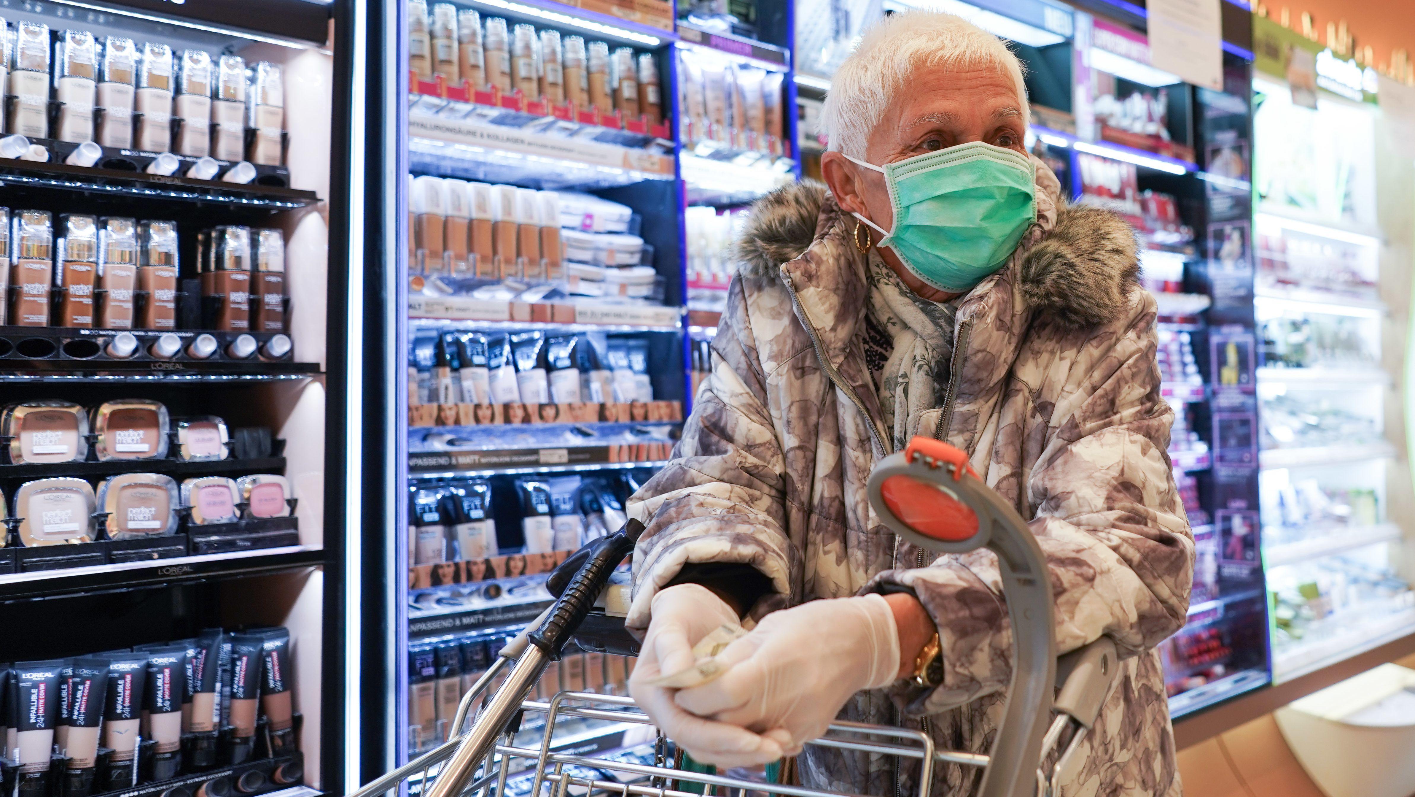 Frau im Supermarkt mit Handschuhen und Mundschutz