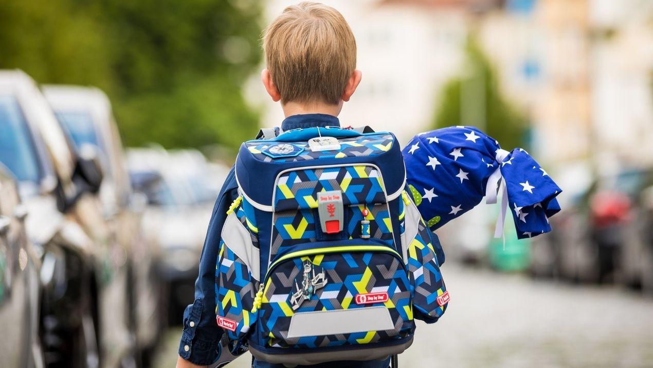 Erster Schultag: ein Junge mit Schultüte auf einer Straße