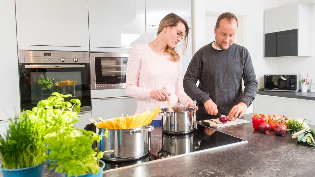 Paar beim Kochen: Ein Topf Spaghetti steht auf dem Herd, eine Frau rührt Soße im zweiten Topf, während ein Mann eine Zwiebel schneidet.