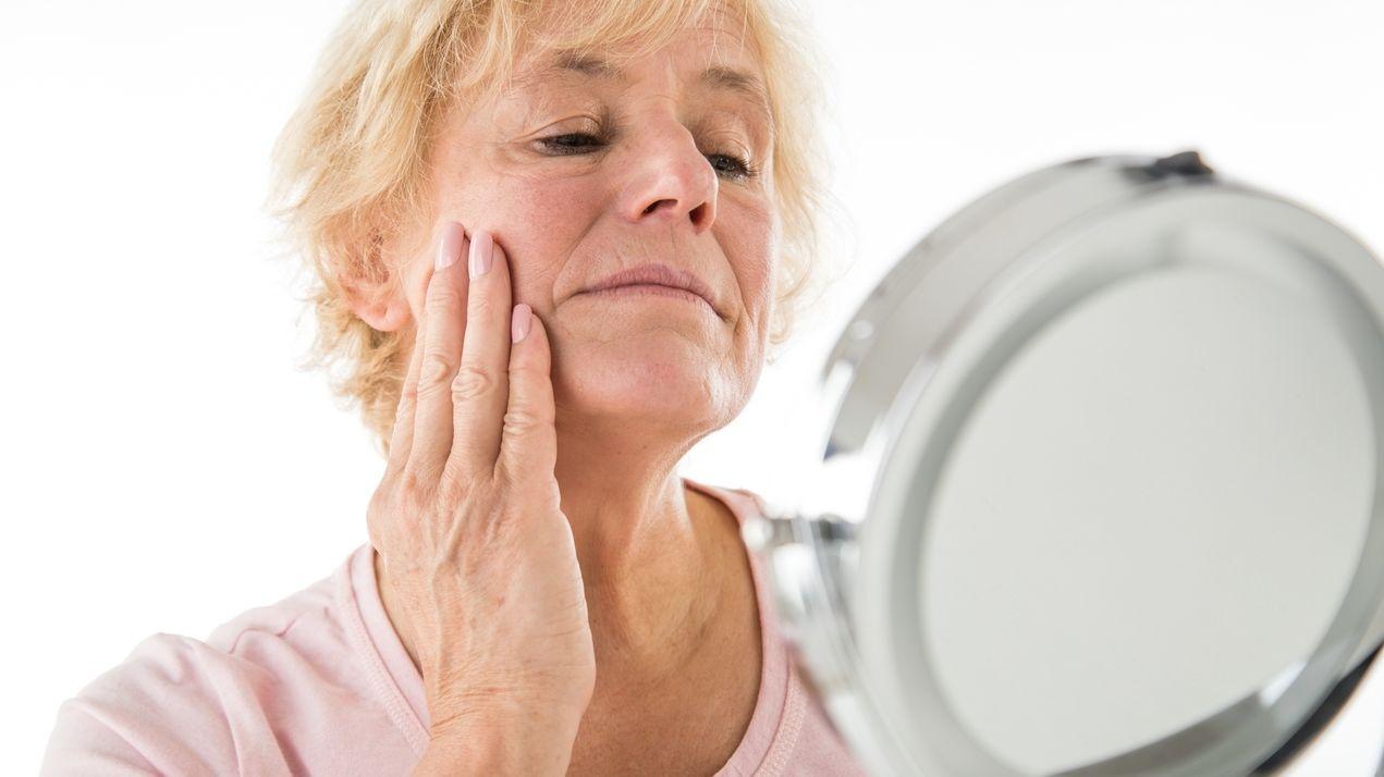 Frau schaut prüfend ihre Haut im Spiegel an