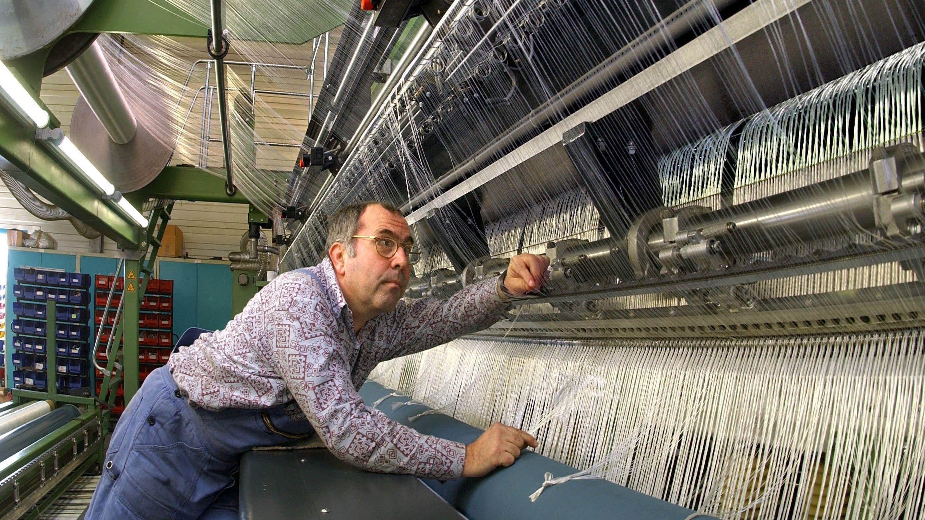 Ein Mitarbeiter prüft Fäden an einer großen Maschine.