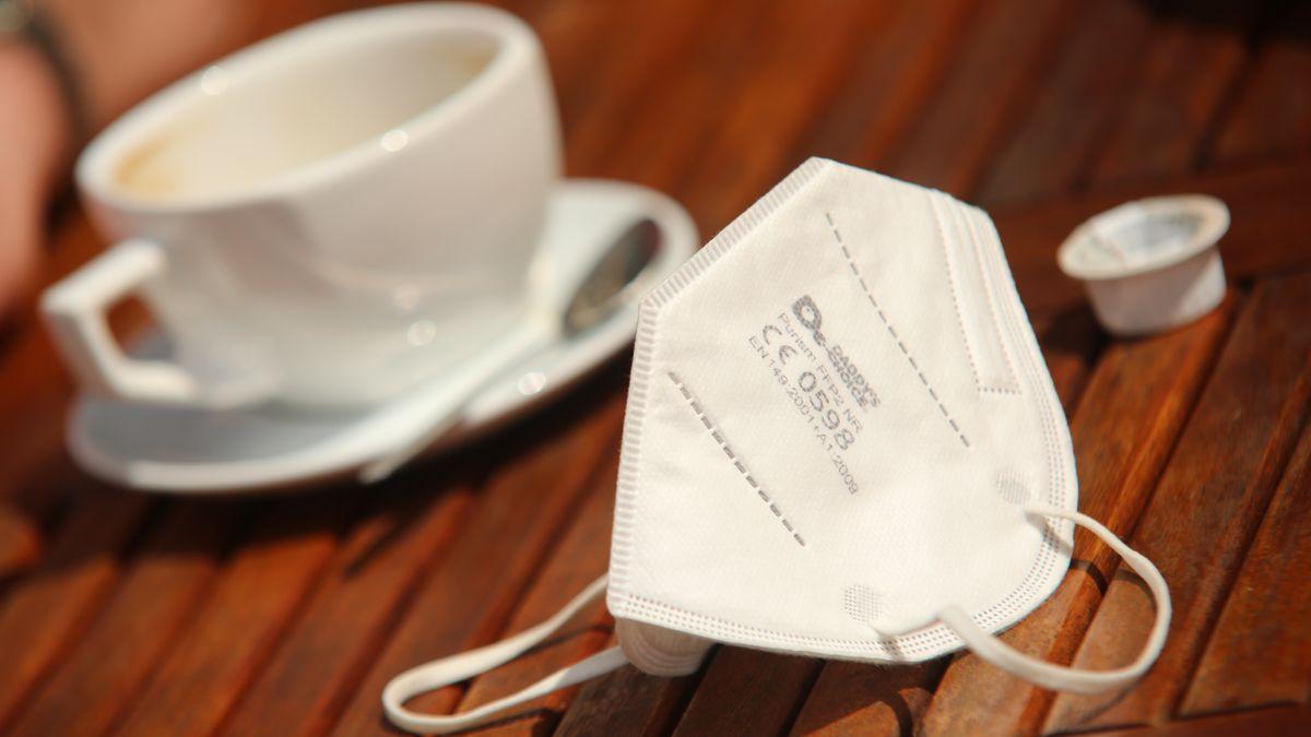 Corona-Maske und Kaffee im Hintergrund; nun steigen die Inzidenz-Zahlen vielerorts wieder leicht. Was hat das zu bedeuten?