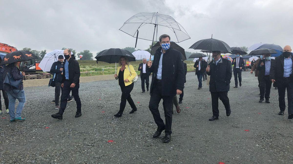 Mit Schirm und Maske treffen die Politiker in Niederbayern ein, um den Donauausbau offiziell zu eröfnnen.