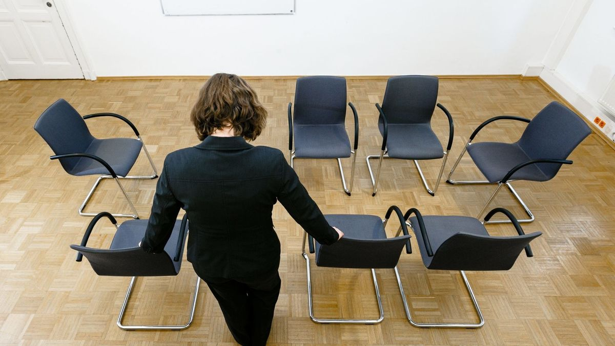 Eine Frau bereitet Stühle für eine Gruppen-Sitzung vor.