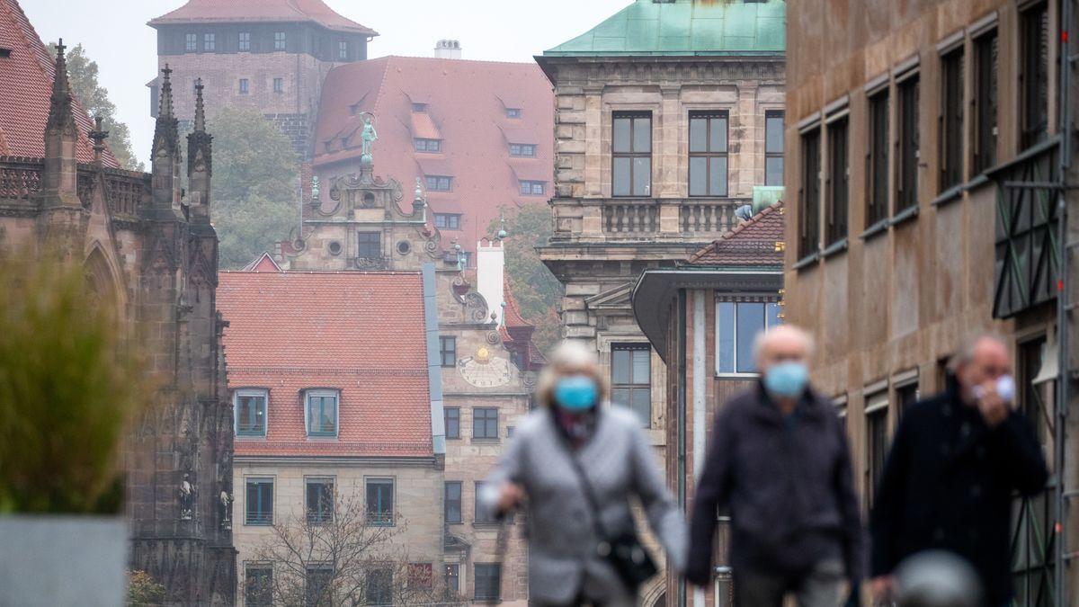 Menschen laufen mit Mund-Nasen-Schutz durch Nürnberg