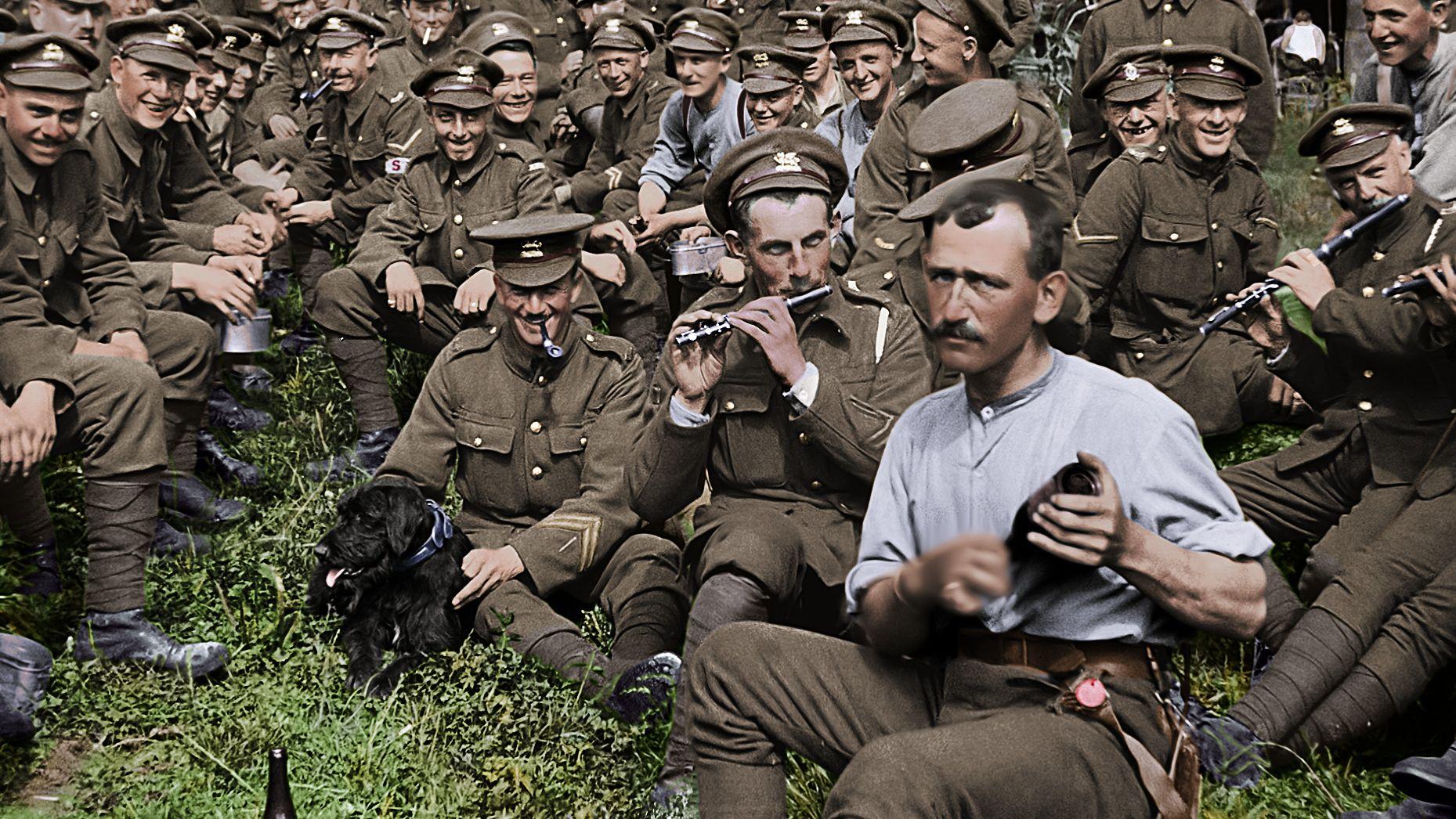 Musizierende Soldaten sitzen in einer Wiese und lachen in die Kamera