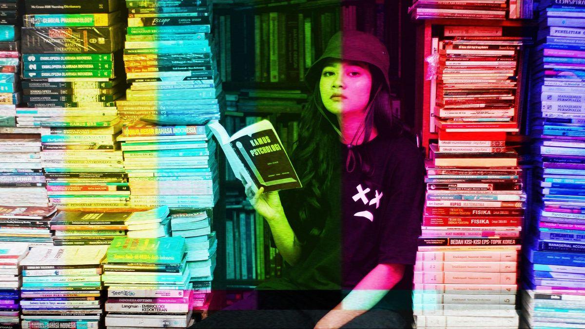 Junge Frau sitzt zwischen Bücherstapeln und schaut von ihrem Buch auf in die Kamera