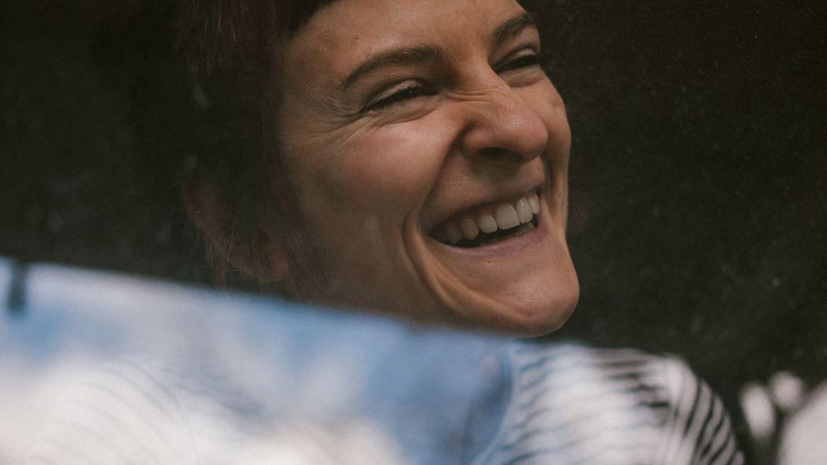 Eine junge Frau lacht. Die Spiegelung im Fensterglas lässt erahnen, dass sie hinter einer Scheibe ist.
