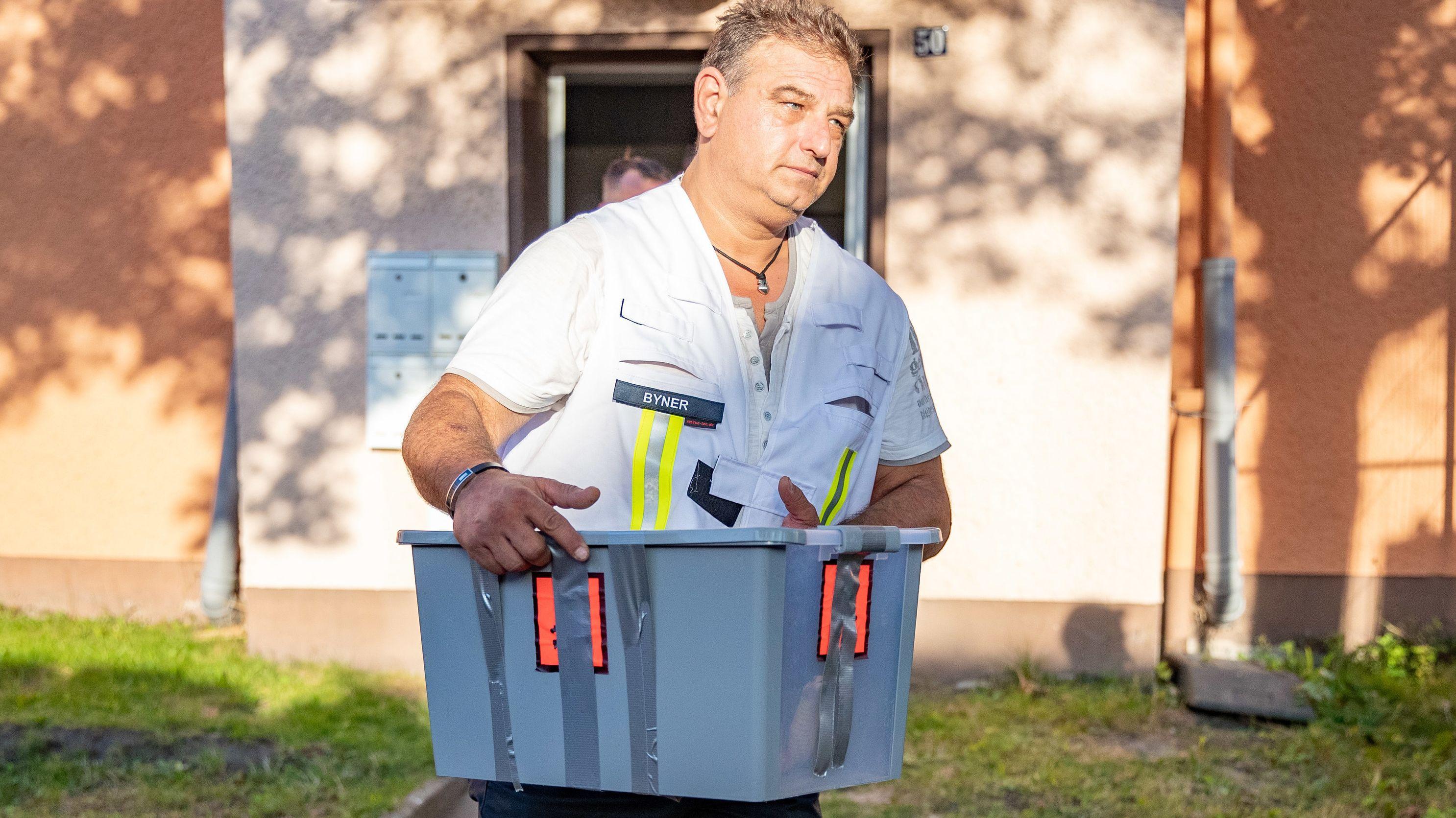 Reptilienexperte Roland Byner trägt die entwischte Monokelkobra in einem Behälter aus dem Gebäude