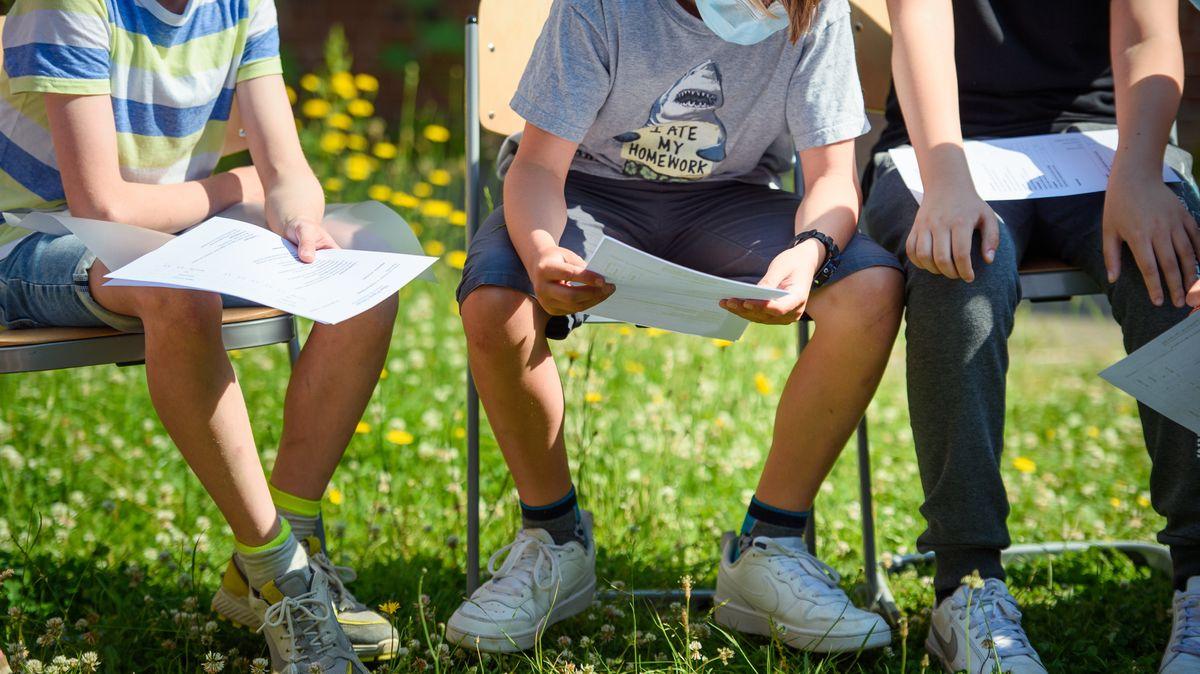 Drei Jungen einer sechsten Klasse reden am letzten Schultag vor den Sommerferien über ihre Zeugnisse