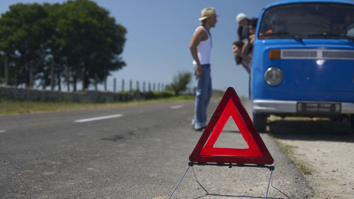 Menschen mit Warndreieck stehen neben Auto auf einer Landstraße.