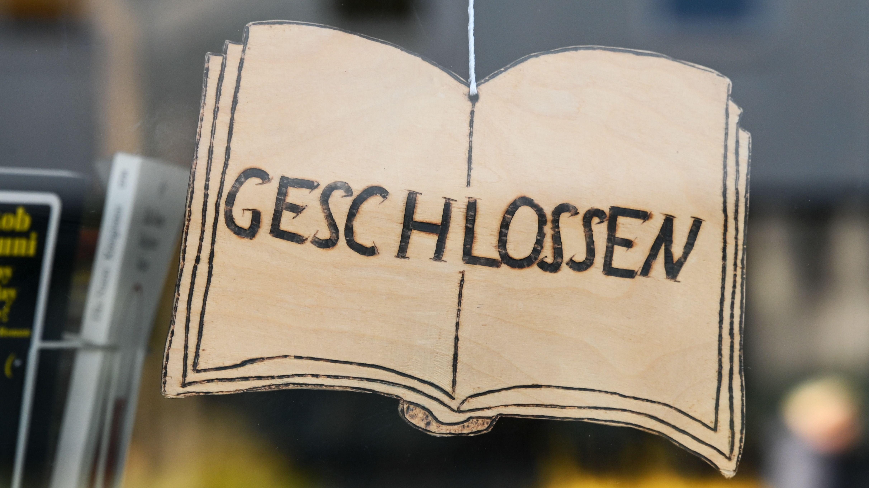 """Ein """"Geschlossen-Schild"""" hängt im Fenster eines Buchladens"""