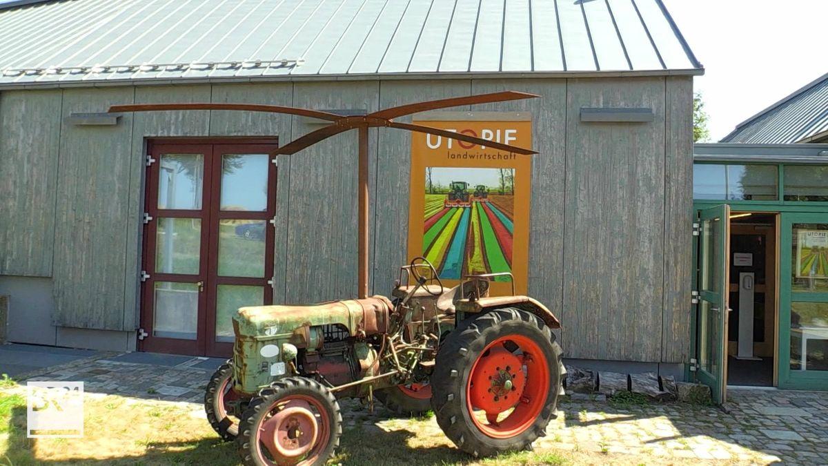 """Ein alter, rostiger Traktor steht vor dem Bauernhofmuseum Kleinlosnitz, dahinter hängt an der Wand ein Plakat mit der Aufschrift """"Utopie Landwirtschaft""""."""