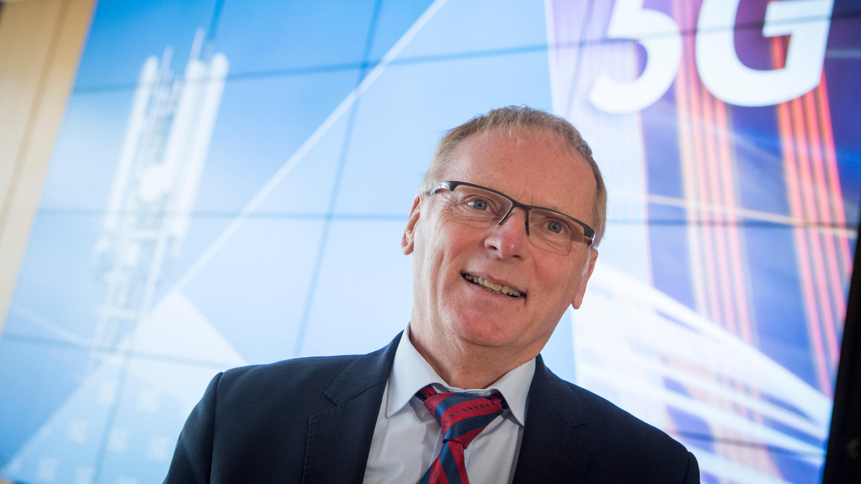 """Jochen Homann, Präsident der Bundesnetzagentur, steht vor einer Leinwand mit der Aufschrift """"5G"""""""