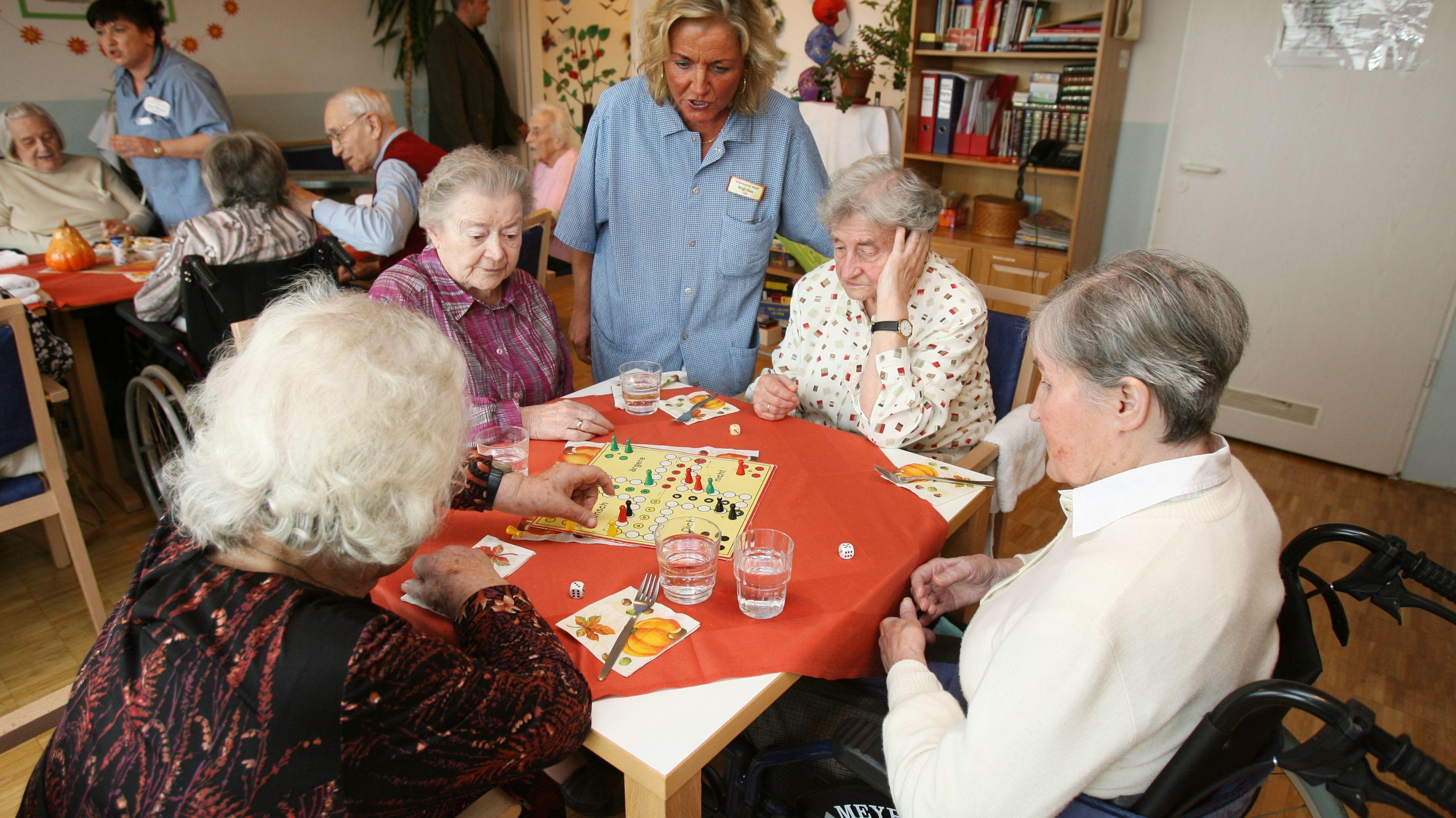 Senioren an einem Tisch und spielen ein Brettspiel.