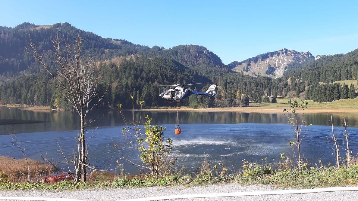 Hubschrauber füllt Löschsack mit Wasser aus dem Spitzingsee.