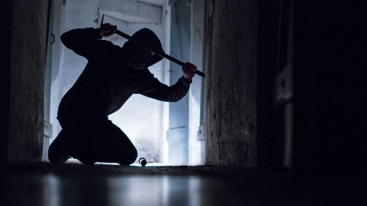 Jemand bricht mit einem Brecheisen in eine Gebäude ein.