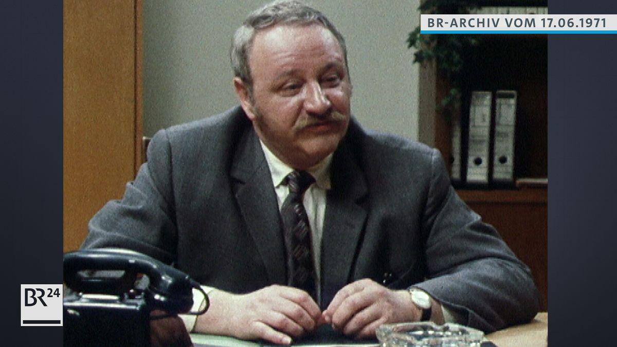 Gustl Bayrhammer am Schreibtisch sitzend