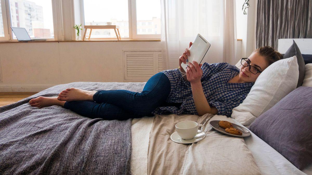 Leserin macht es sich auf dem Bett gemütlich