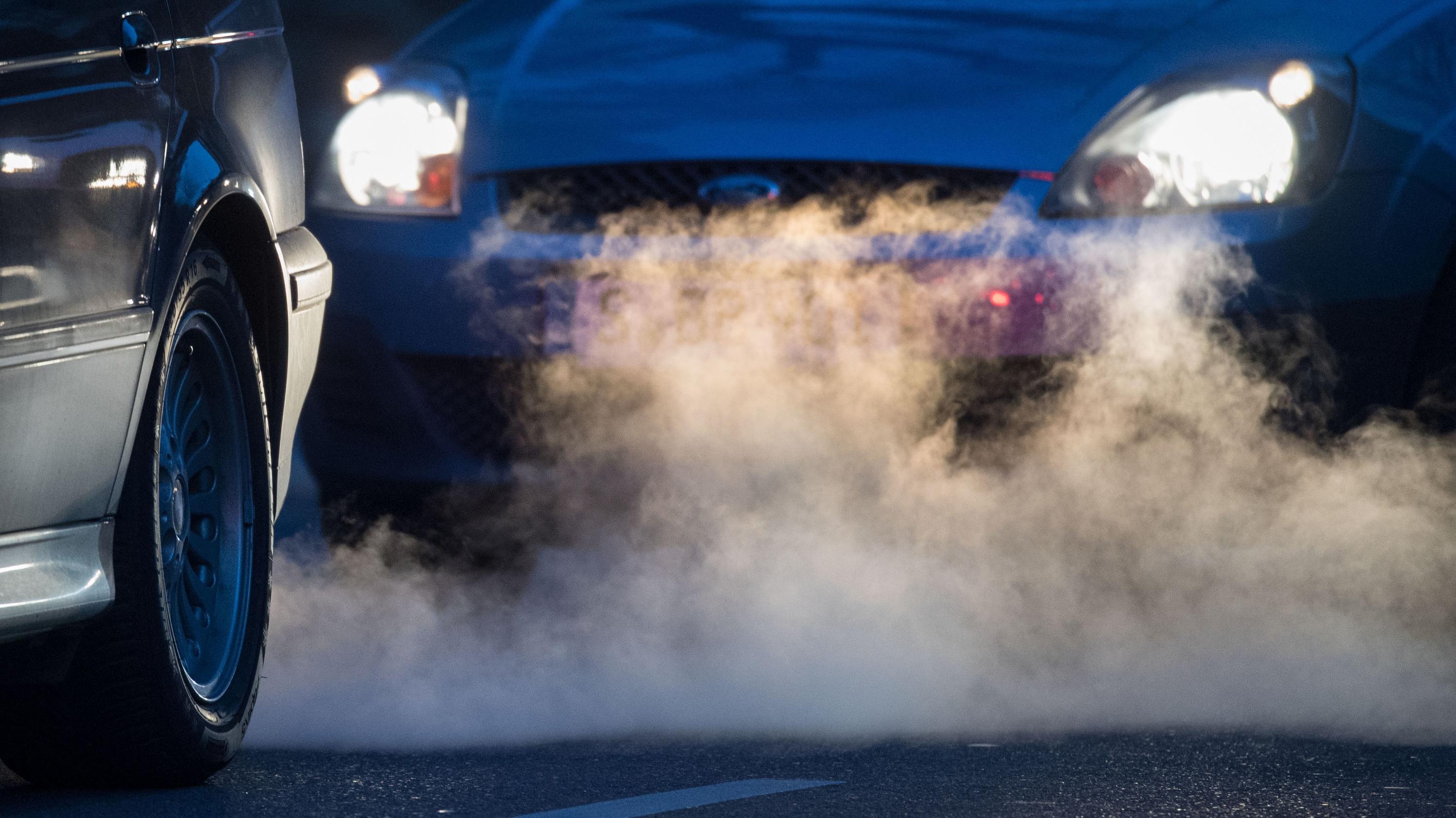 Zwei Autos stehen auf einer Straße hintereinander. Zwischen ihnen ist eine Wolke Abgase.