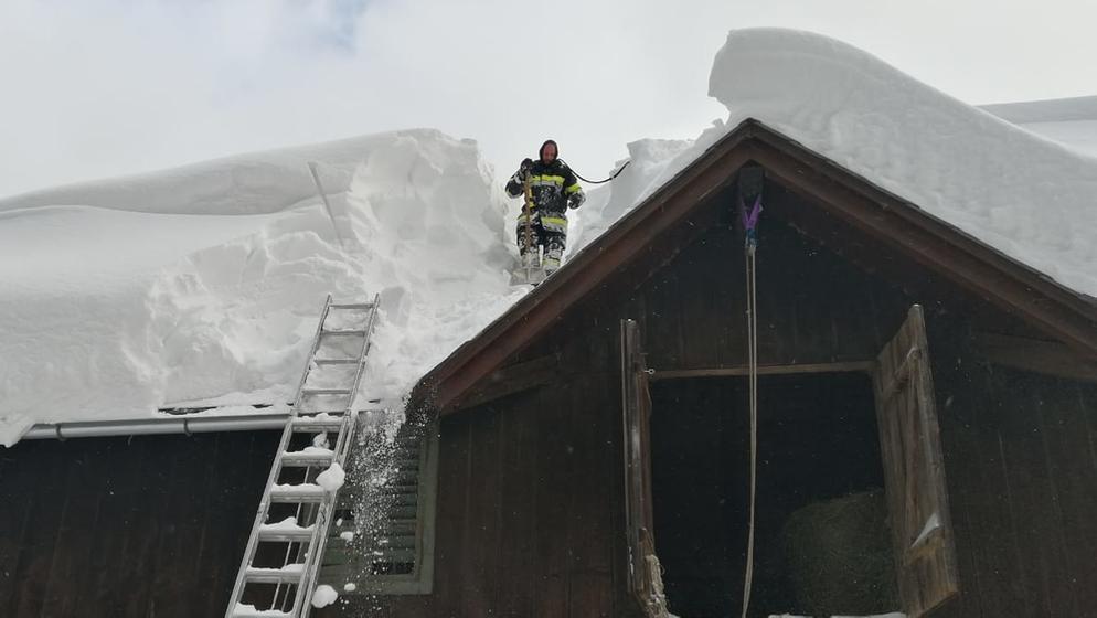 Ein Feuerwehrmann befreit ein Dach von seiner Schneelast.  | Bild:dpa-Bildfunk