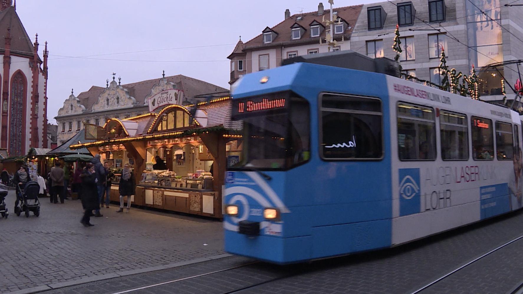 Straßenbahn fährt an Würzburger Weihnachtsmarkt vorbei