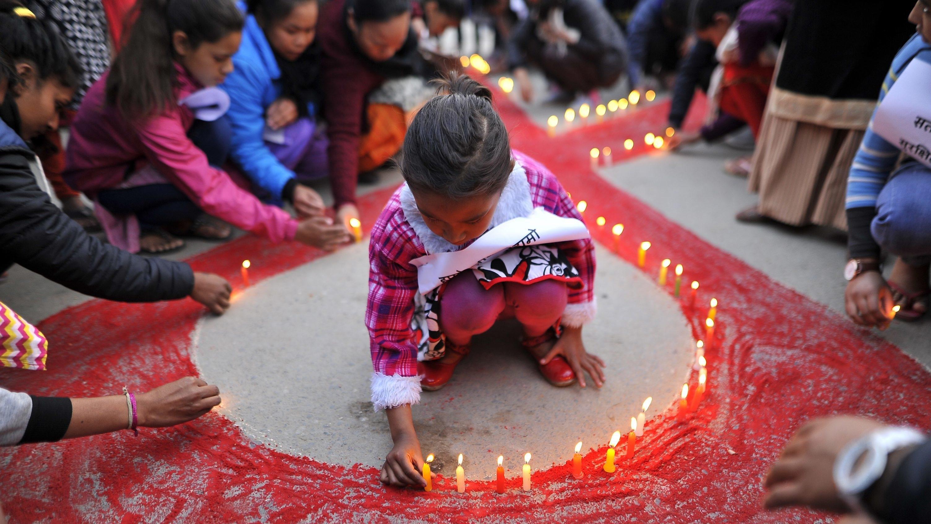 Kinder in Nepal schmücken zum Welt-Aids-Tag eine Aids-Schleife mit Kerzen