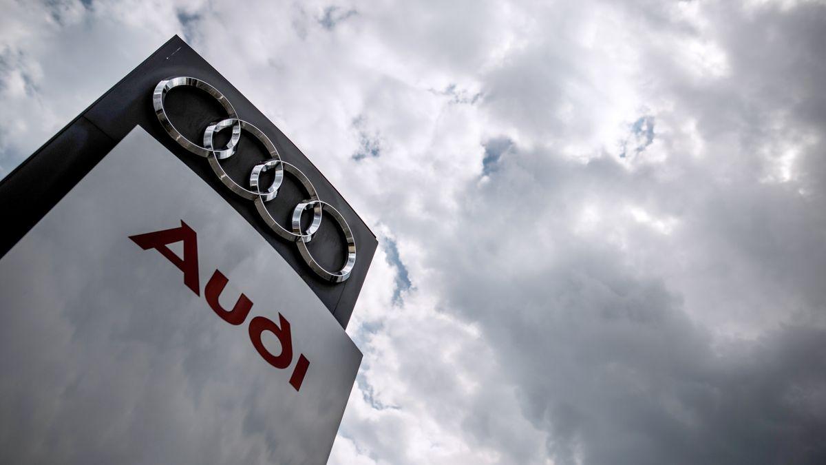 """Das Schild eines Audi-Händlers mit dem Schriftzug """"Audi"""" und den vier Ringen von unten fotografiert, darüber der wolkenverhangene Himmel"""