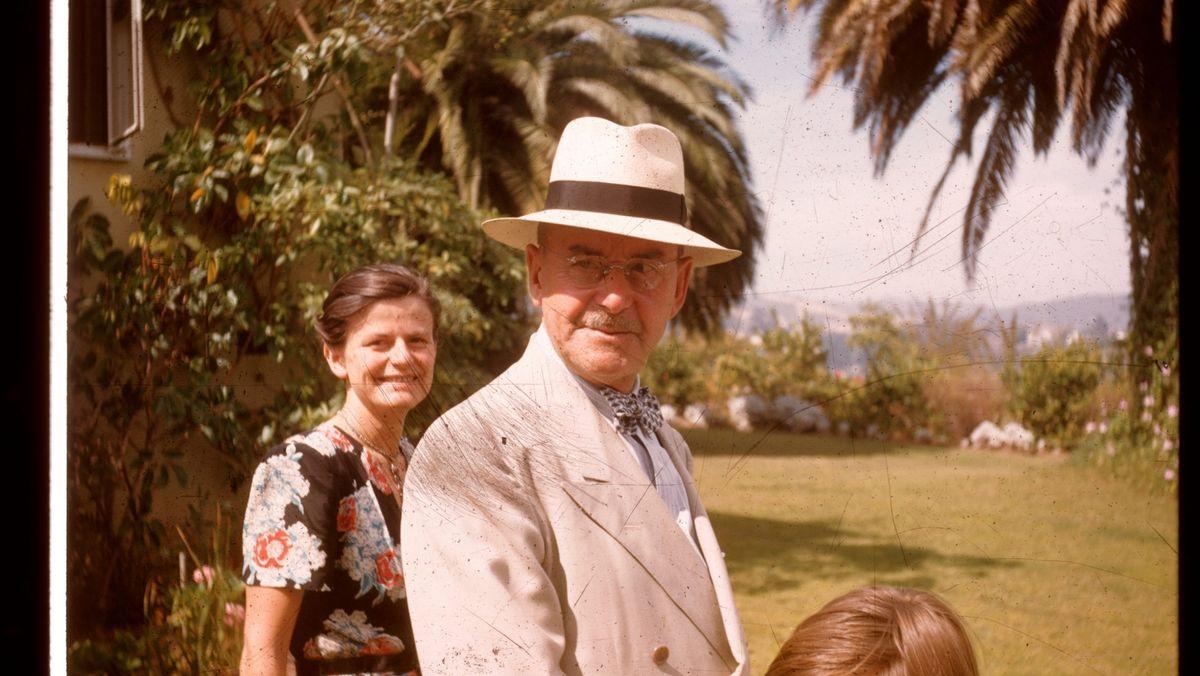 Thomas Mann 1946 mit seiner Tochter Elisabeth und einem Kind im Garten seiner Villa in Pacific Palisades, im Hintergrund ein Rasen und Palmen.