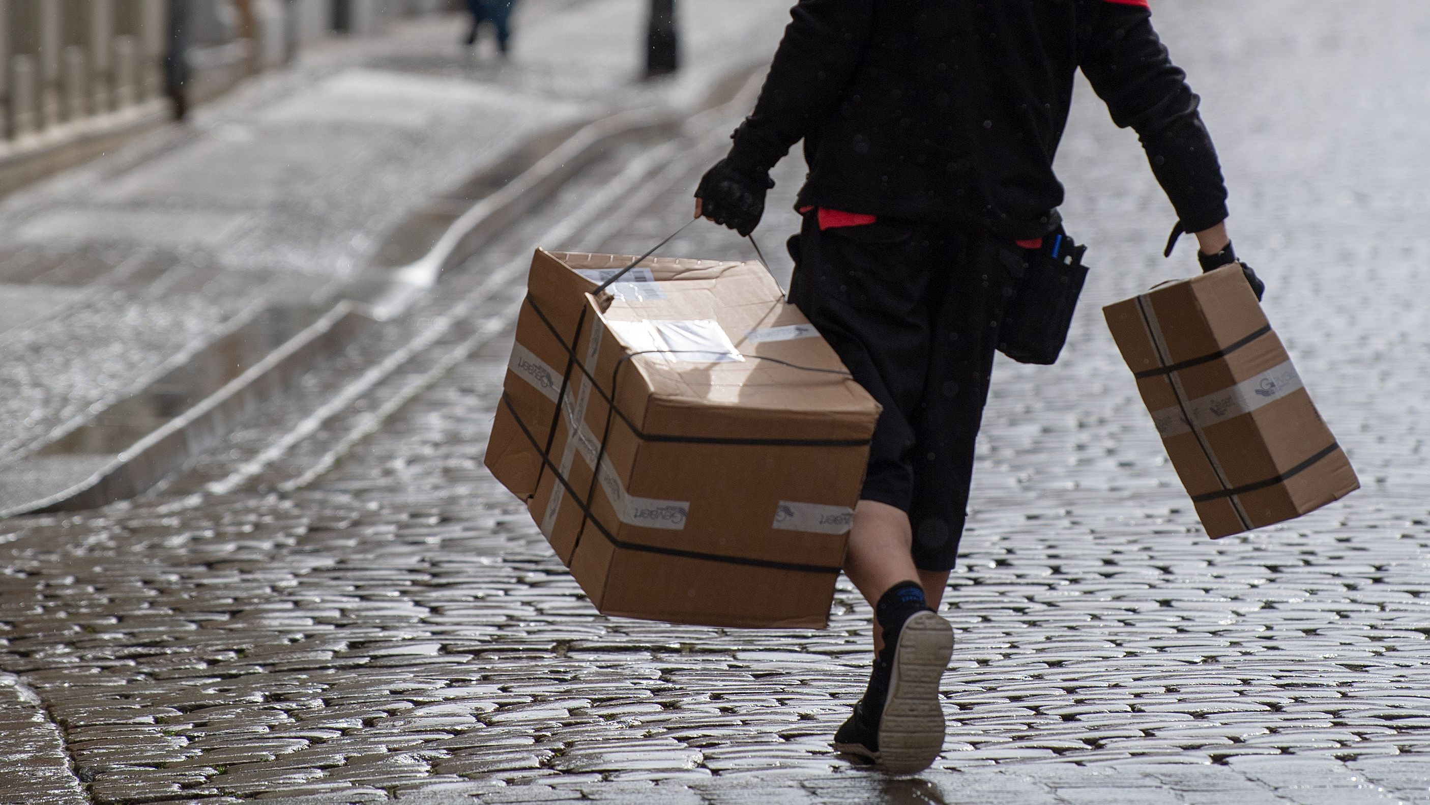 Ein Paketzusteller schleppt zwei Pakete eine Straße entlang.