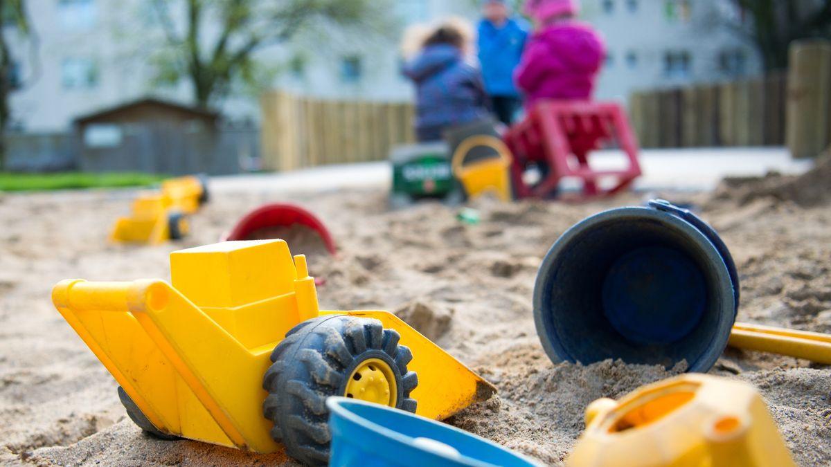 Spielzeug liegt in einem Sandkasten während Kinder spielen in einer Kindertagesstätte.