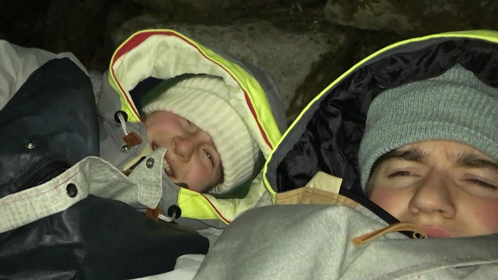 Zwei Menschen sind in jeweils einem Sheltersuit eingemummelt