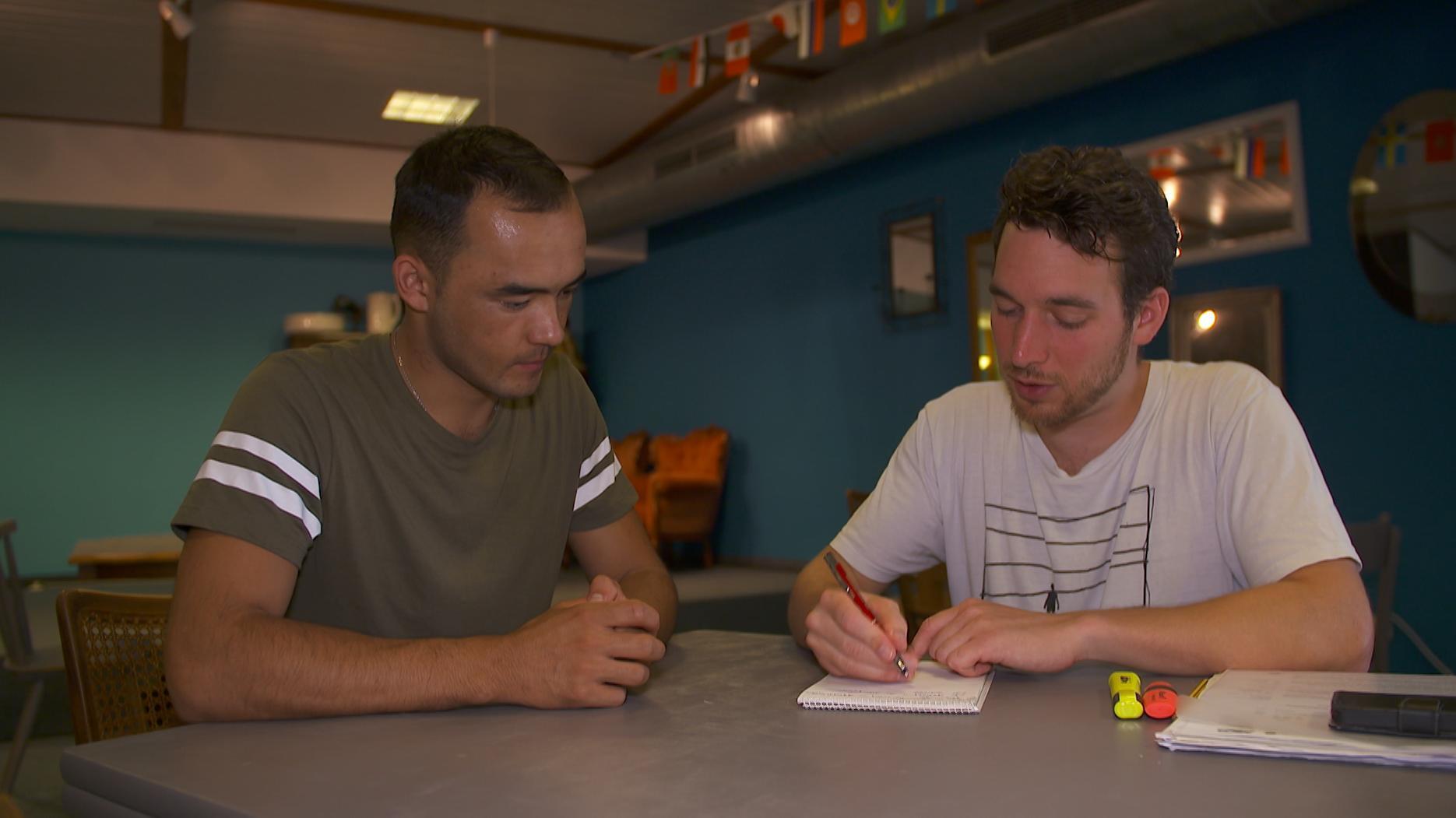 Junger Mann aus Afghanistan und deutschr Flüchtlingehelfer sitzen an Tisch in Cafe