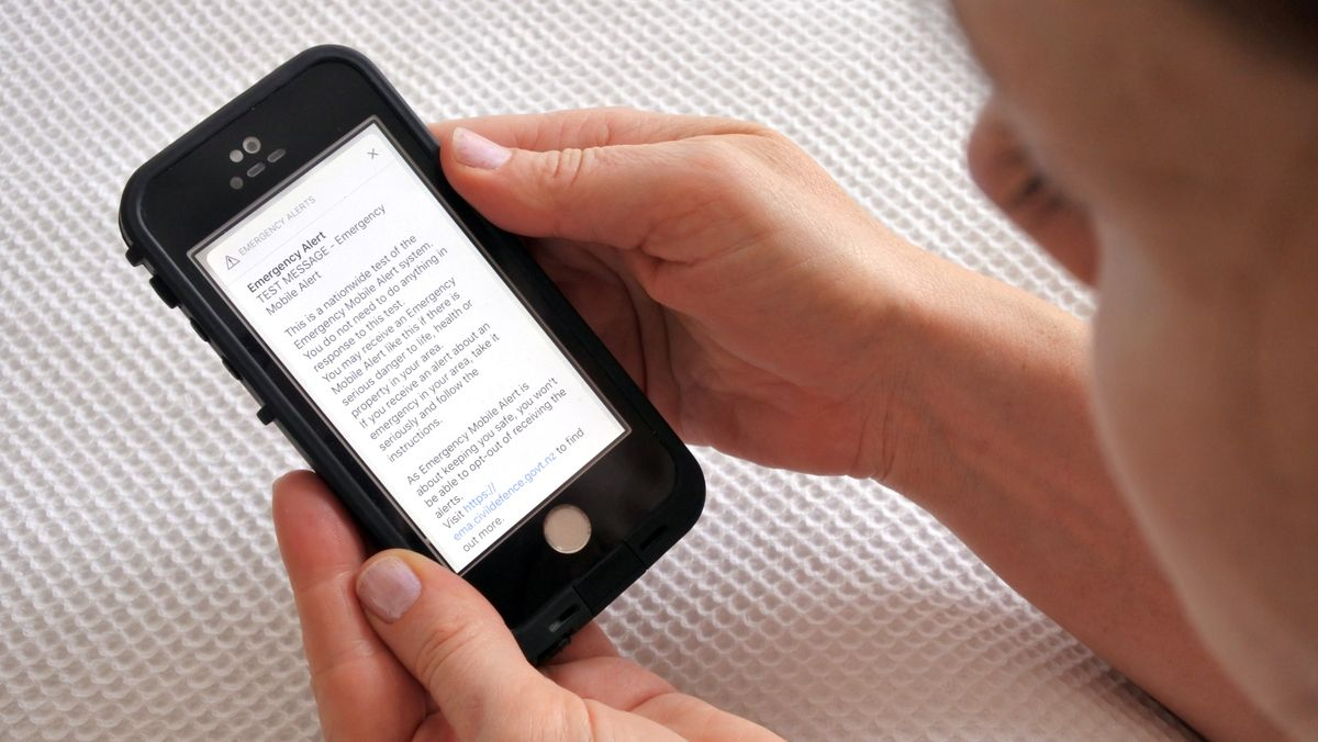Eine Person liest eine Notfall-Warnung auf ihrem Mobiltelefon.