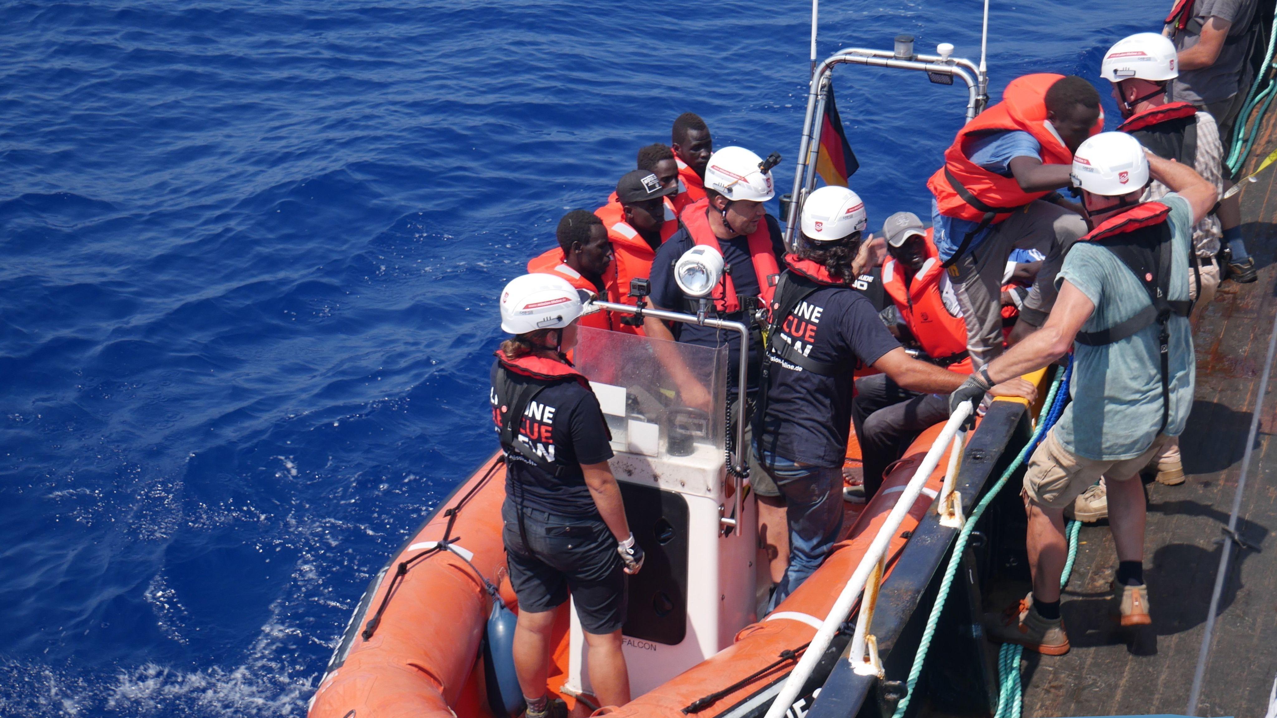 Gerettete verlassen Schlauchboot und gehen an Bord eines Schiffes