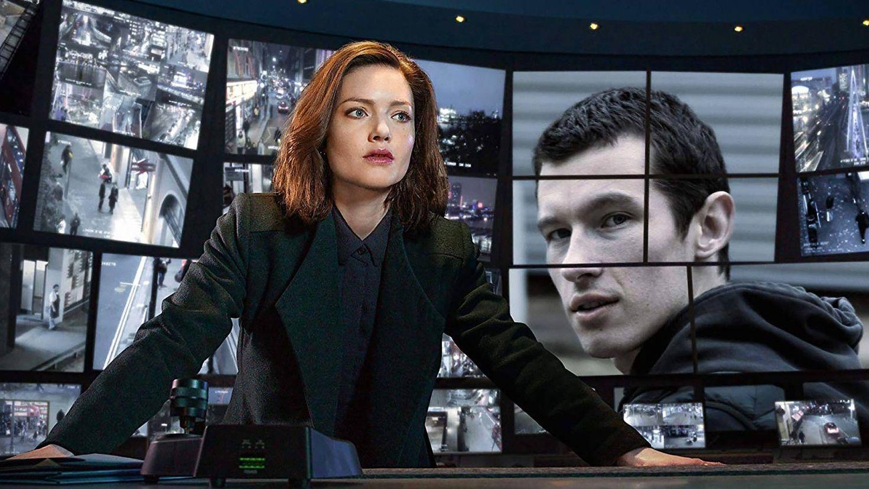 """Eine Polizistin steht vor einer Wand Videoüberwachungsbildschirmen und blickt konzentriert in die Ferne in einer Szene aus der BBC-Serie """"The Capture""""."""