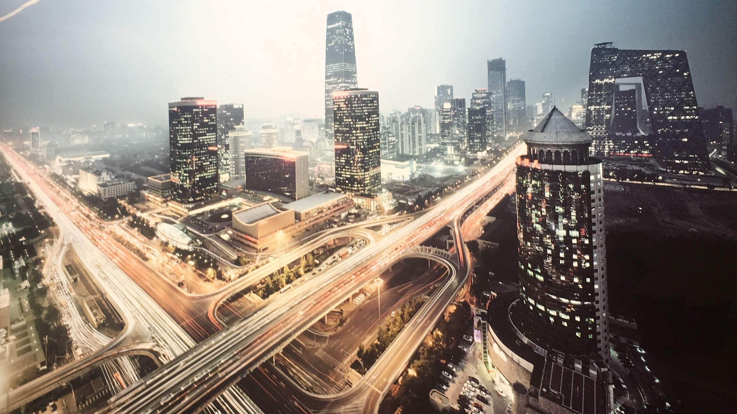 Eine Großstadt mit Wolkenkratzern bei Nacht, zwischen denen sich Stadtautobahnen vorbeiziehen.