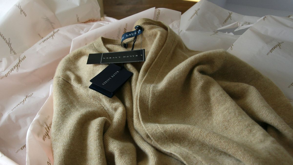 Ein Pullover der Marke Ralph Lauren liegt zwischen Seidenpapier auf einem Tisch.
