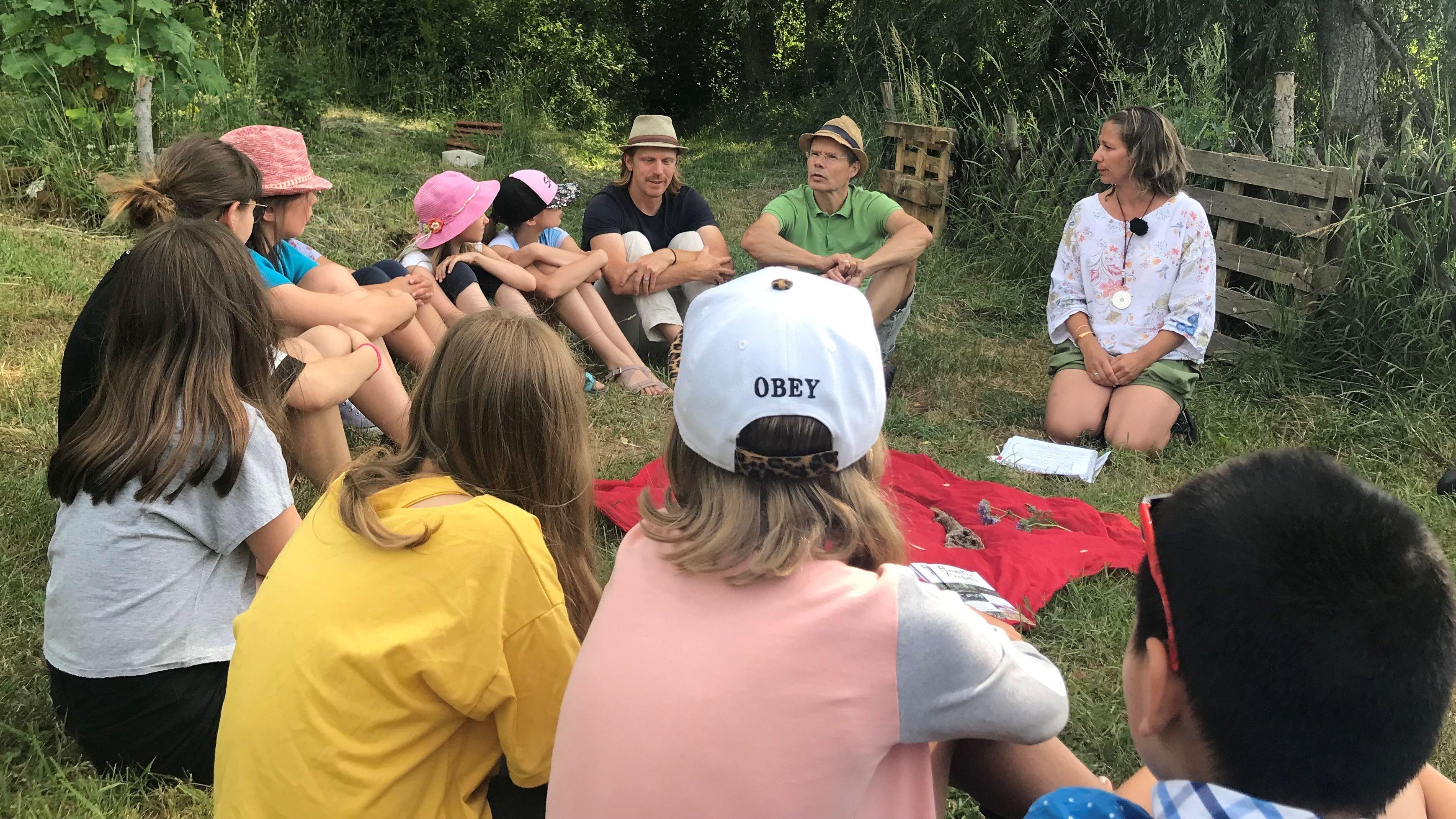 Eine Schulklasse und mehrere Erwachsene sitzen in einem Garten im Kreis.