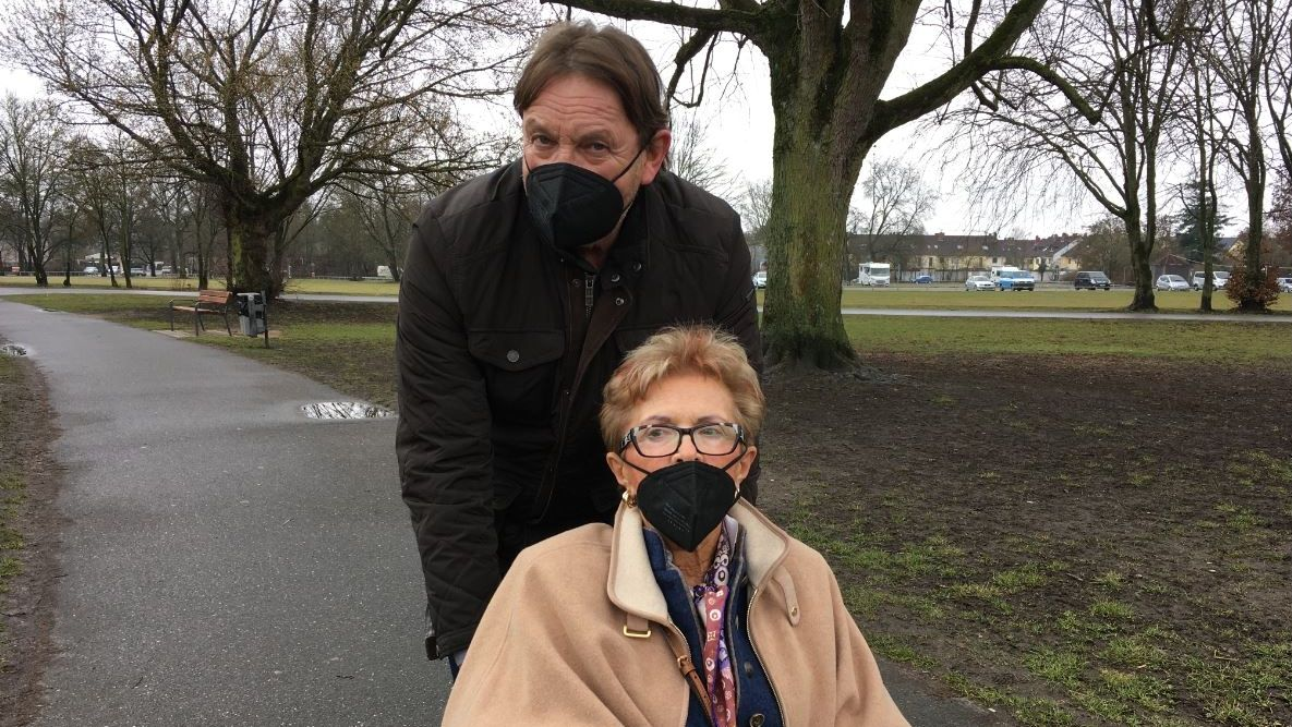Personenschützer Peter Althof schiebt eine Frau im Rollstuhl durch einen Park