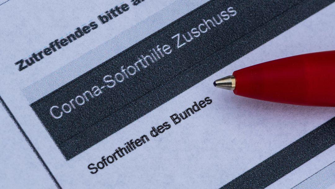 Ein Stift liegt auf einem Antrag für den Corona-Soforthilfe-Zuschuss