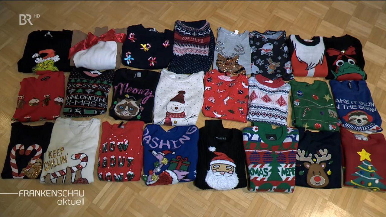 24 Weihnachtspullover nebeneinander auf dem Boden.